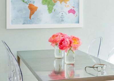 A modern classic colonial table, chairs, map of the world, pink flowers, perspect chairs